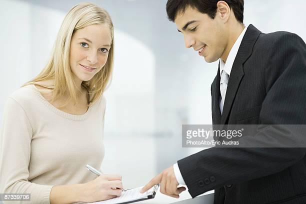 Businessman holding out clipboard, woman writing on document and smiling at camera