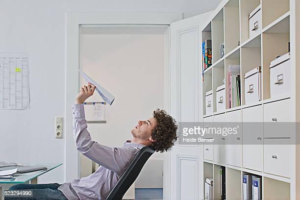businessman holding paper airplane - verveling stockfoto's en -beelden