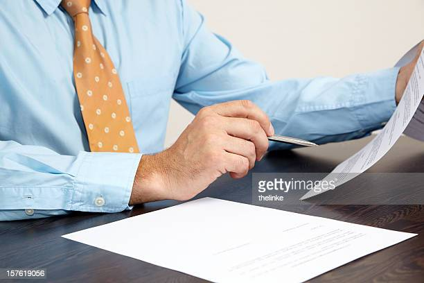 A businessman holding papers at a desk