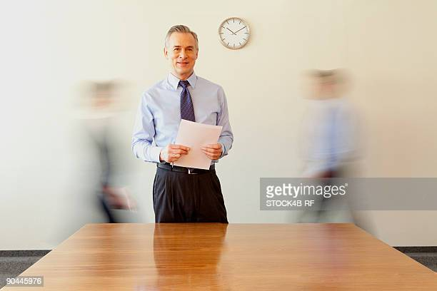businessman holding papers with people in background passing by, munich, bavaria, germany - incidental people stock pictures, royalty-free photos & images