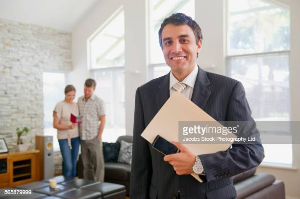 Businessman holding paperwork in living room of clients