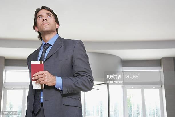 Empresario sostiene pasaporte y pasaje aéreo