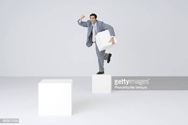businessman holding pedestal block, shaking fist - pedestal stock pictures, royalty-free photos & images