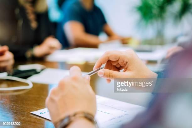 empresário, segurando a caneta enquanto discutia com os colegas de mesa de reuniões no escritório criativo - mesa de reunião - fotografias e filmes do acervo