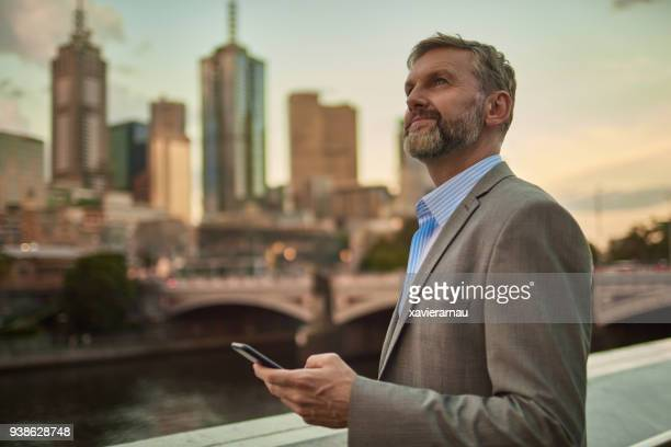 businessman holding phone at dusk in melbourne centre city - looking up stock pictures, royalty-free photos & images