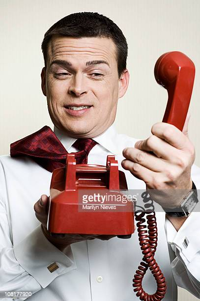 businessman holding phone away from him - funny customer service stock pictures, royalty-free photos & images