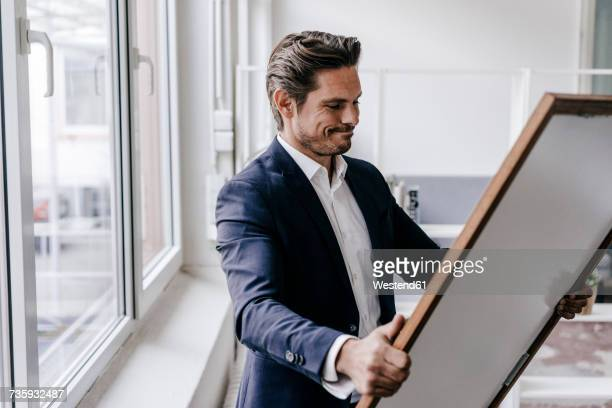 businessman holding picture frame - art dealer stock pictures, royalty-free photos & images