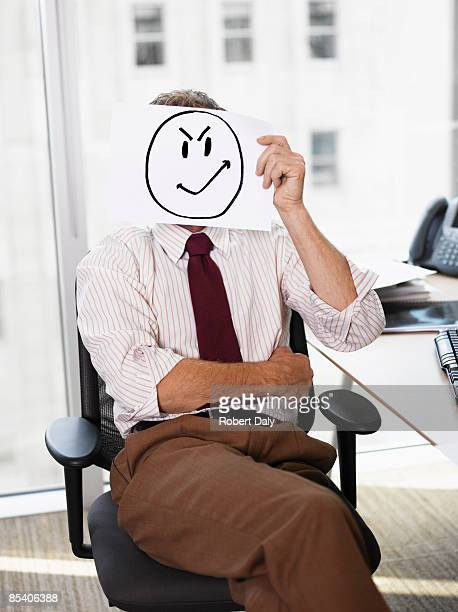 Businessman holding picture of angry face