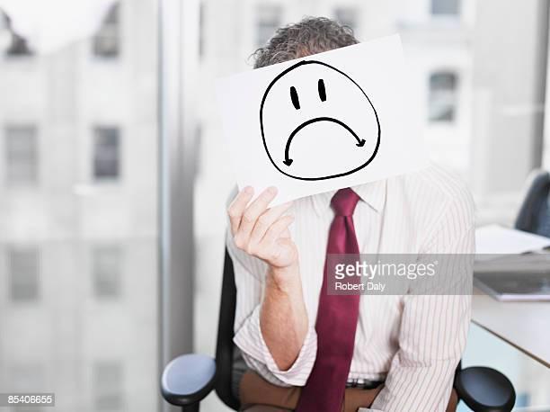 Empresario sosteniendo una imagen de tristeza cara