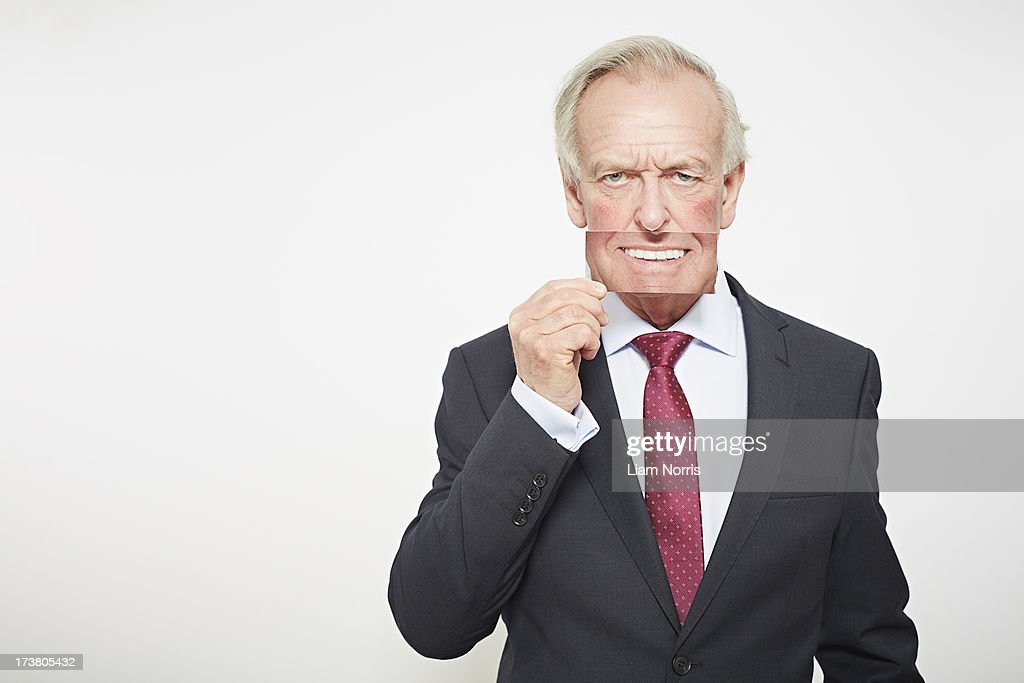 Businessman holding picture over his mouth : Stock Photo