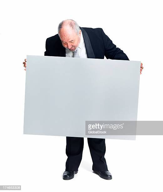 Businessman holding placard against white background
