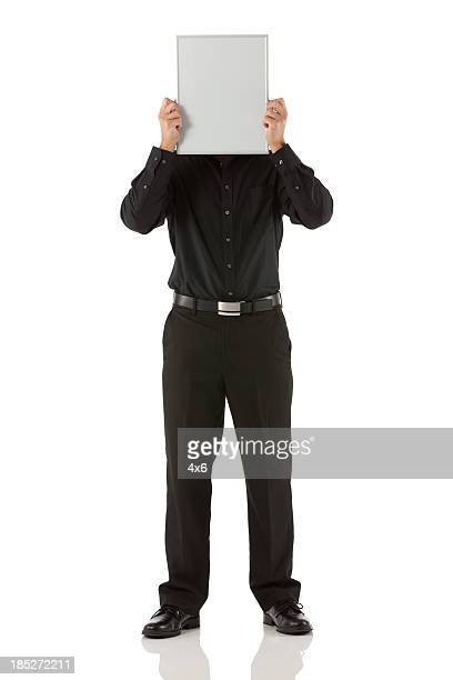Businessman holding placard in front of face