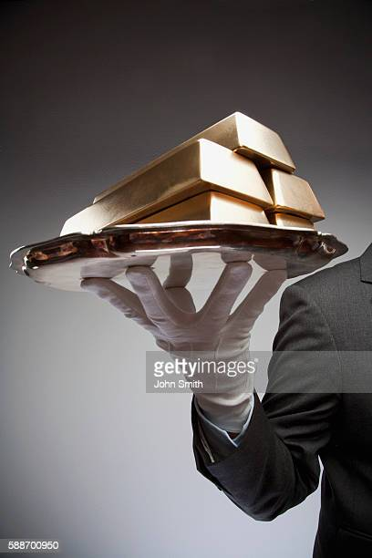 Businessman holding platter with gold bars