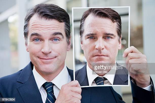 Businessman holding portrait of himself