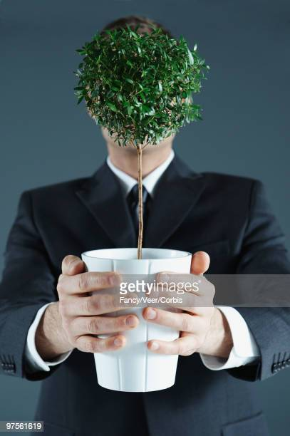 Businessman holding potted plant covering his face