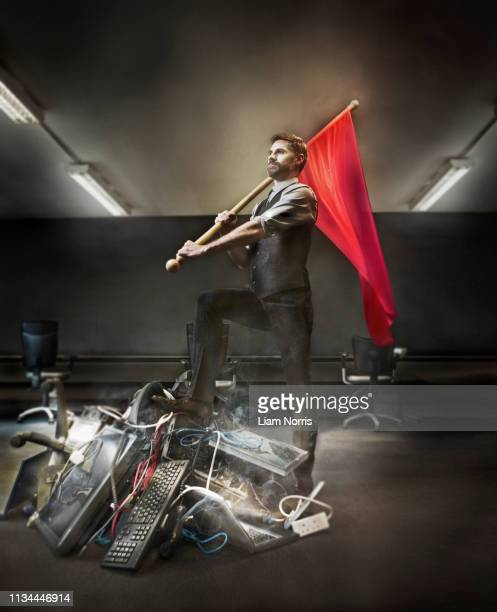 businessman holding red flag on pile of computer equipment - 旗 ストックフォトと画像