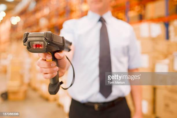 Empresario sostiene escáner en el almacén.