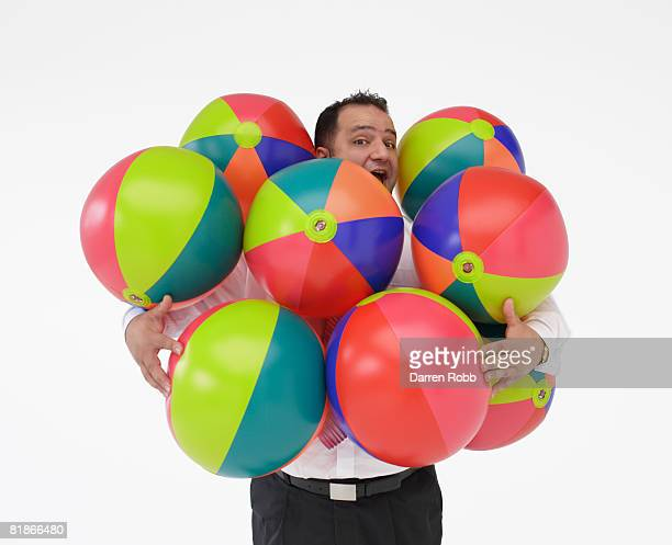 Businessman holding several inflatable beach balls, laughing