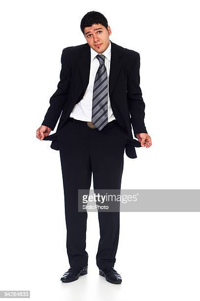 Businessman holding showing his empty pockets isolated on white background