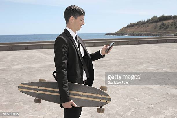 Businessman holding skateboard and mobile device