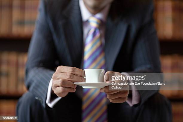 businessman holding small coffee cup and saucer