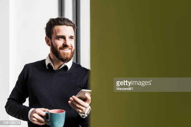 Businessman holding smart phone, talking