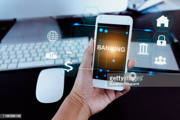 businessman holding smart phone use word banking in hand with icon network connection on virtual screen dark background - 銀行 ストックフォトと画像