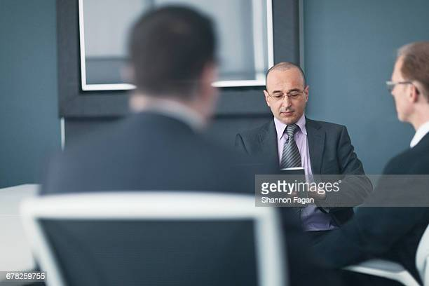 Businessman holding smart tablet in office meeting