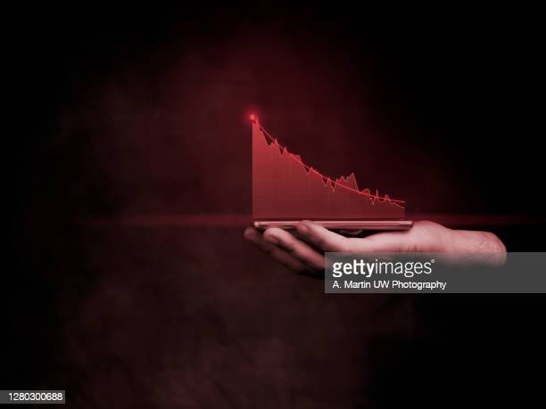 businessman holding smartphone and showing holographic graphs and stock market statistics lost profits. concept of growth planning and business strategy. display of bad economy form digital screen. - number stock pictures, royalty-free photos & images