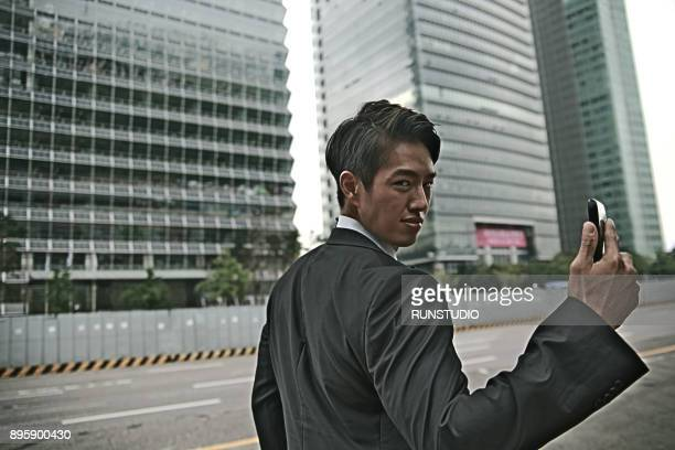 Businessman holding smartphone in city
