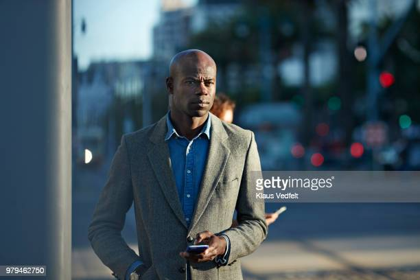 Businessman holding smartphone & waiting for the tram in San Francisco