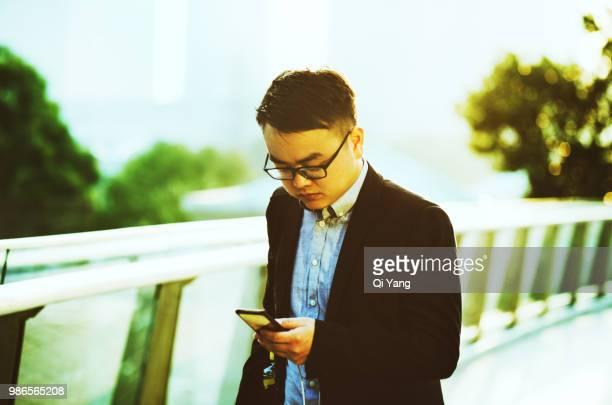 Businessman holding smartphone walking on the bridge