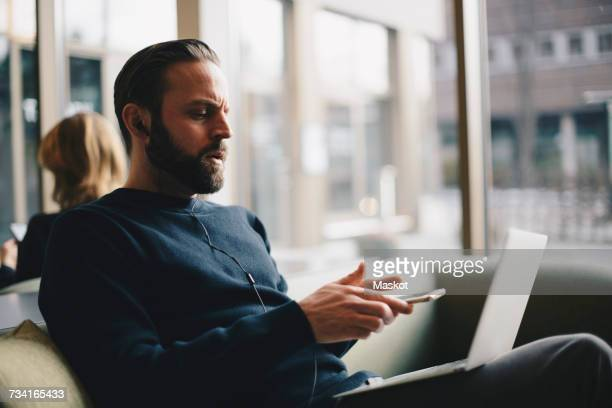 Businessman holding smartphone while usign laptop at office lobby