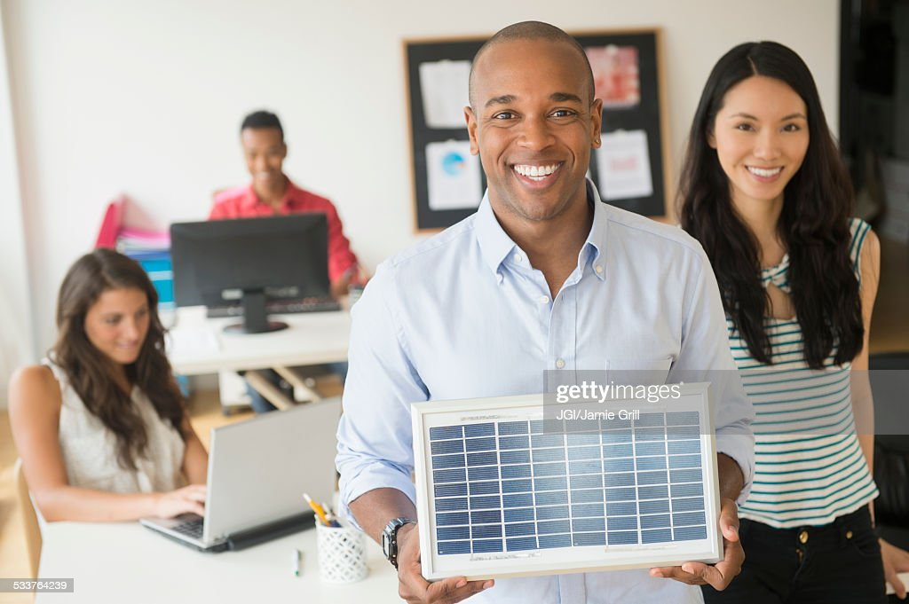 Businessman holding solar panel model in office : Foto stock