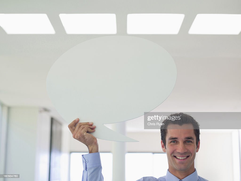Businessman holding speech balloon : Stock Photo