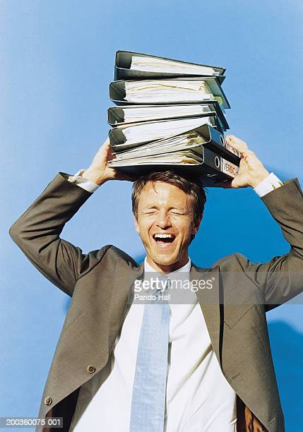 Businessman holding stack of files on head, eyes closed, mouth open