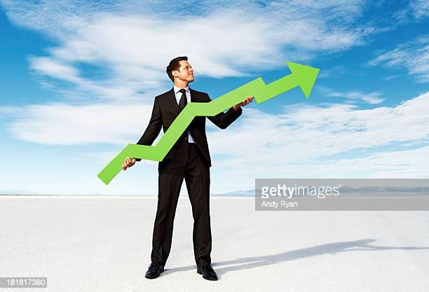 Businessman holding stock arrow on salt flats.