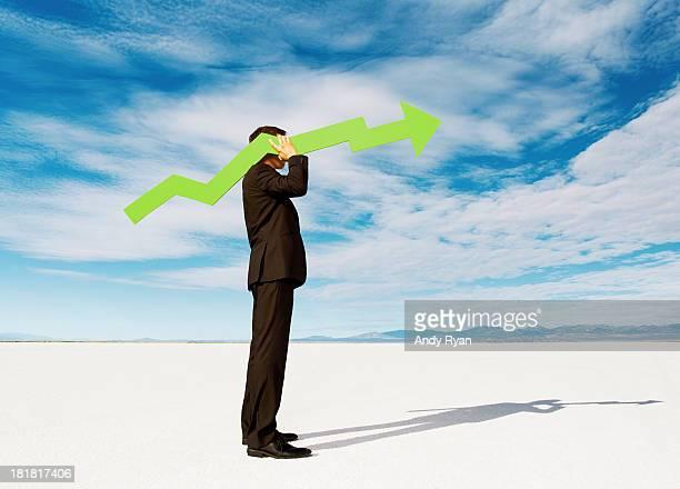 Businessman holding stock ticker arrow in desert.