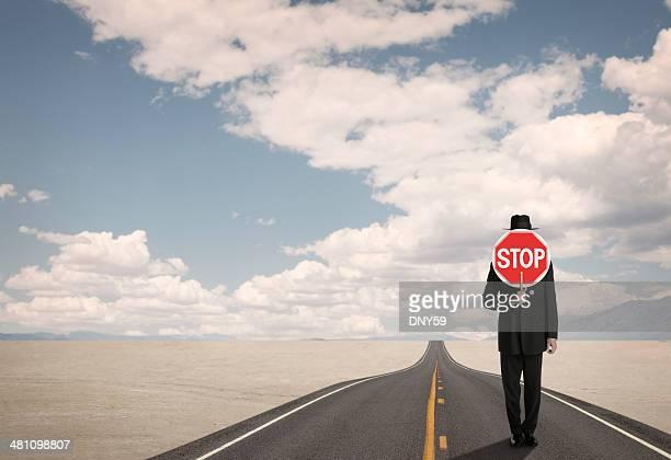 Homme d'affaires tenant le panneau stop sur la route dans le désert avec télécommande