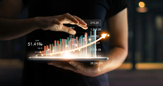 Businessman holding tablet and showing a growing virtual hologram of statistics, graph and chart with arrow up on dark background. Stock market. Business growth, planing and strategy concept. 1051659174