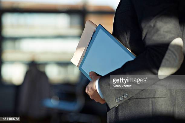 Businessman holding tablet, newspaper and Notebook