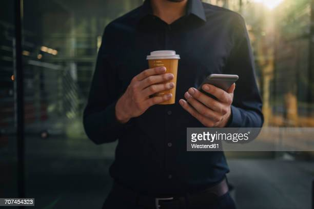 Businessman holding takeaway coffee and smartphone