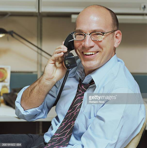 Businessman holding telephone receiver, smiling