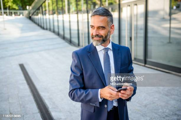 businessman holding the phone in front of a business center - solo un uomo foto e immagini stock