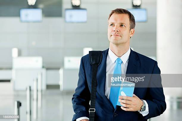 Businessman Holding Travel Tickets At Airport