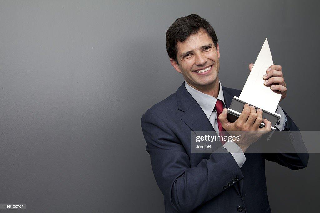 Businessman holding trophy : Stock Photo