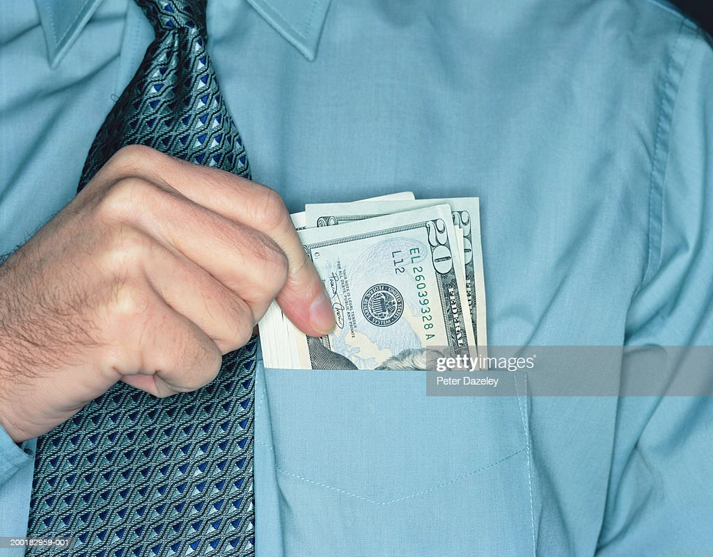 Businessman holding twenty dollar notes in shirt pocket, close-up : Stock Photo