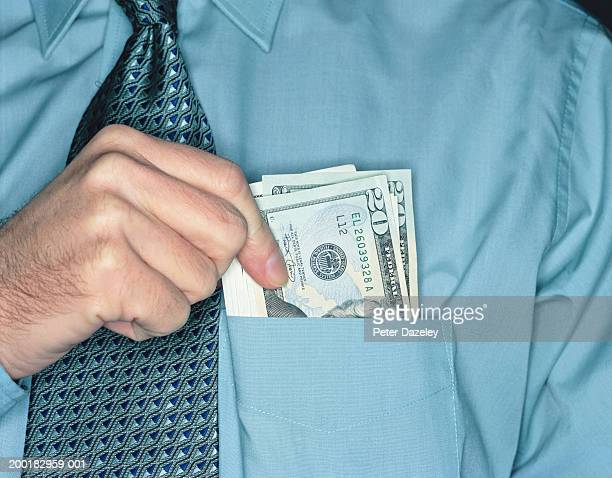 businessman holding twenty dollar notes in shirt pocket, close-up - falsenews stock pictures, royalty-free photos & images