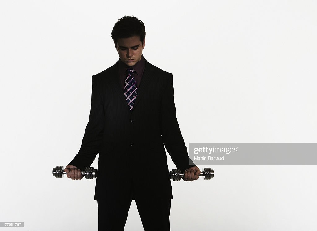 Businessman holding two small free weights : Stock Photo