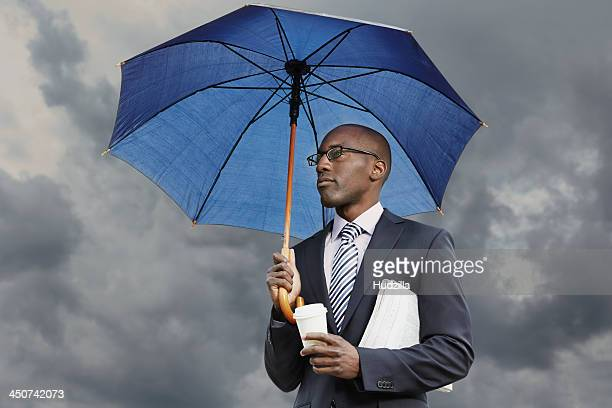 Businessman holding umbrella, disposable coffee cup and newspaper under a moody sky